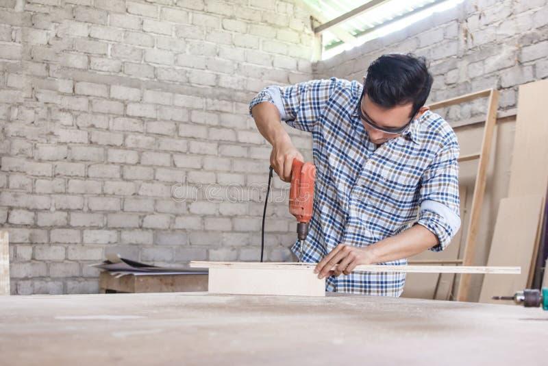 Arbeitskraft an der Tischlerwerkstatt, die Bolzen unter Verwendung des Schraubenziehers installiert lizenzfreie stockfotografie