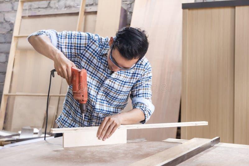 Arbeitskraft an der Tischlerwerkstatt, die Bolzen unter Verwendung des Schraubenziehers installiert lizenzfreies stockbild
