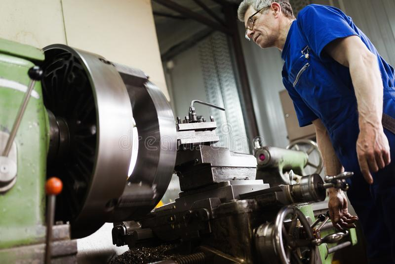Arbeitskraft in der Uniform, die in der manuellen Drehbank in der Metallindustriefabrik funktioniert lizenzfreie stockbilder