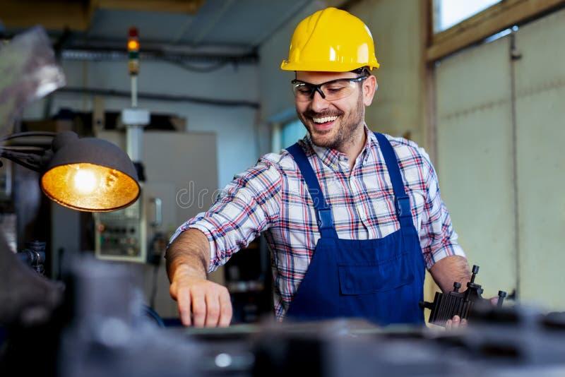 Arbeitskraft in der Uniform, die in der manuellen Drehbank in der Metallindustriefabrik funktioniert stockfotografie