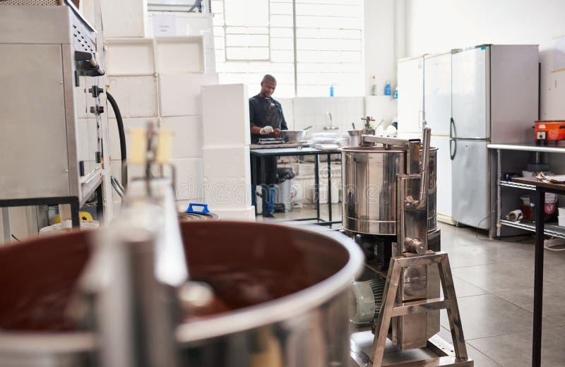 Arbeitskraft, die Bestandteile in einer handwerklichen Schokoladenerzeugungsfabrik vorbereitet stockbild