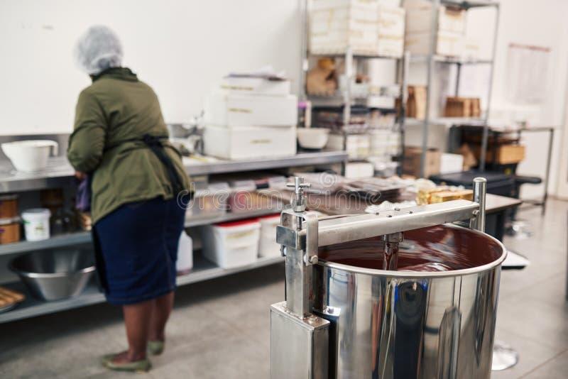 Arbeitskraft, die Bestandteile in einer Schokoladenerzeugungsfabrik vorbereitet stockfoto