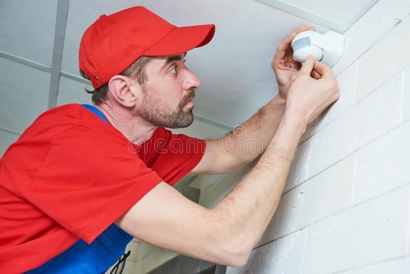 Arbeitskraft, die Bewegungs-Sensor-Detektor auf der Decke installiert oder justiert stockbilder