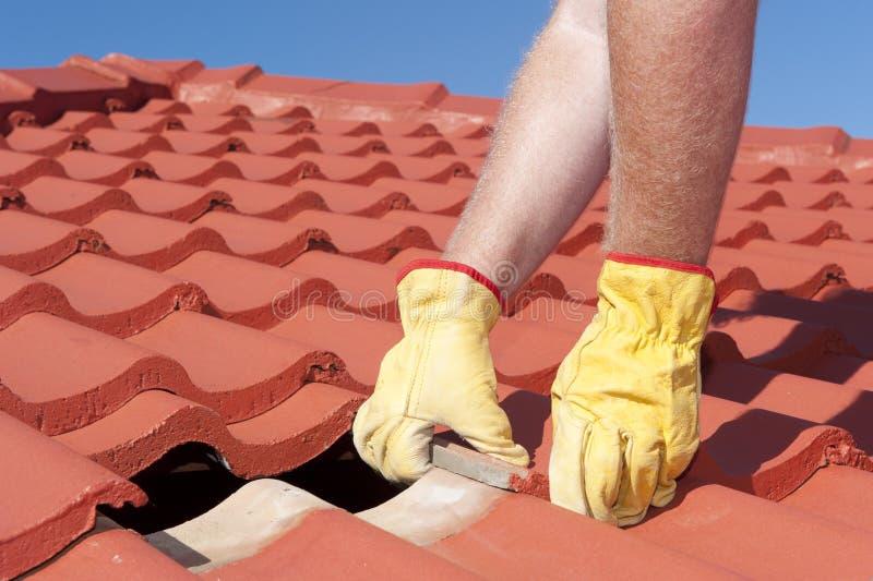 Arbeitskraft, die Dachfliesen auf Haus repariert stockbilder