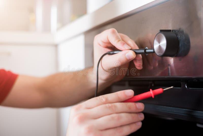 Arbeitskraft, die den Ofen in der Küche repariert stockfotos