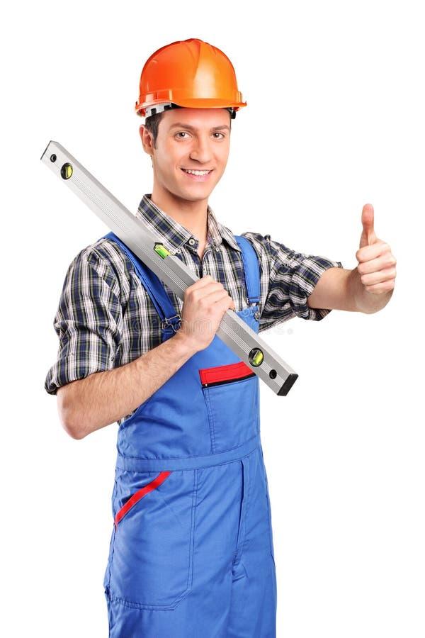 Arbeitskraft, die ein Hilfsmittel anhält und Daumen aufgibt stockbilder
