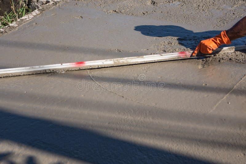 Arbeitskraft, die eine hölzerne Spachtel für Zement nach dem Gießen des Frischbetons verwendet stockfotos