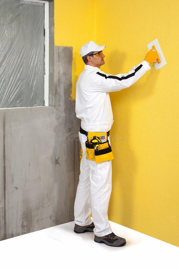 Arbeitskraft, die einen Gips auf einer Wand verbreitet stockbilder