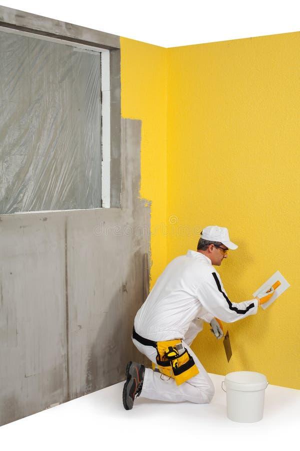 Arbeitskraft, die einen Gips auf einer Wand verbreitet lizenzfreies stockfoto