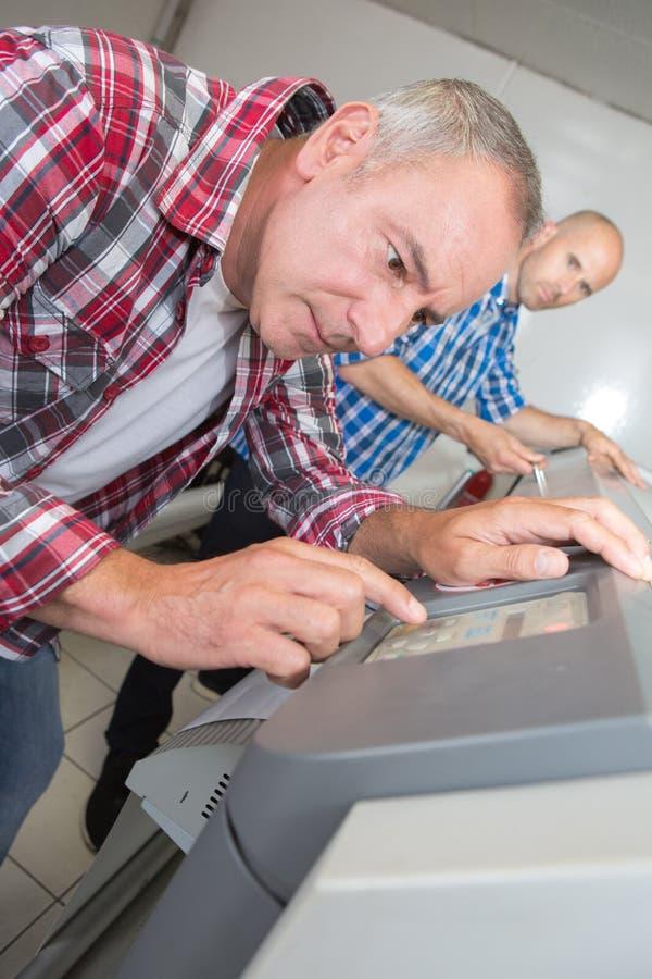 Arbeitskraft, die große Druckerformat-Tintenstrahlfunktion verwendet stockfotos