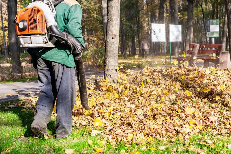 Arbeitskraft, die Hochleistungslaubsauger im Stadtpark betreibt Entfernen von gefallenen Blättern im Herbst Blätter, die oben wir stockbild