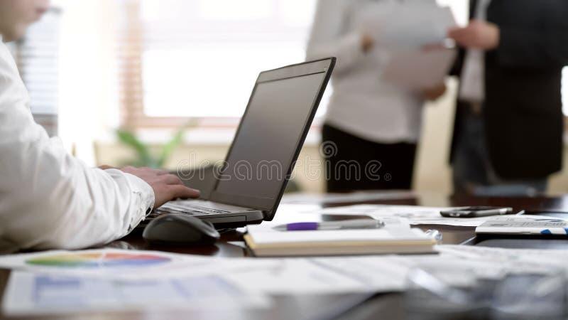 Arbeitskraft, die Kenntnisse über Laptop während zwei Kollegen besprechen Papiere im Büro nimmt stockbilder
