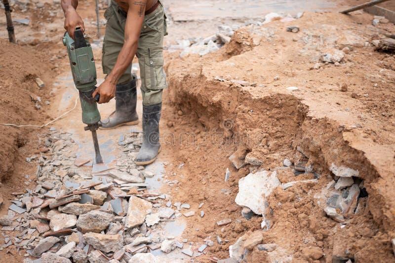 Arbeitskraft, die konkrete Ausziehermaschine verwendet, um Beton zu zerstören lizenzfreie stockfotos