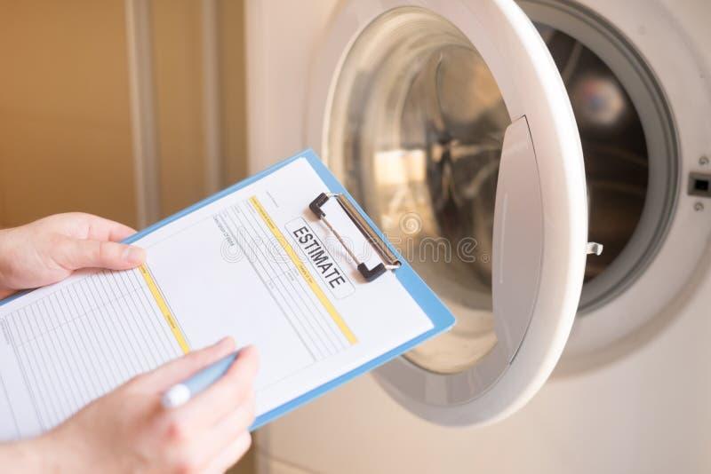 Arbeitskraft, die Kosten für defekte Waschmaschine schätzt stockfotografie