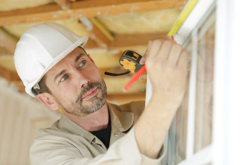Arbeitskraft, die Ma?band Fenster in der Baustelle verwendet lizenzfreie stockfotos