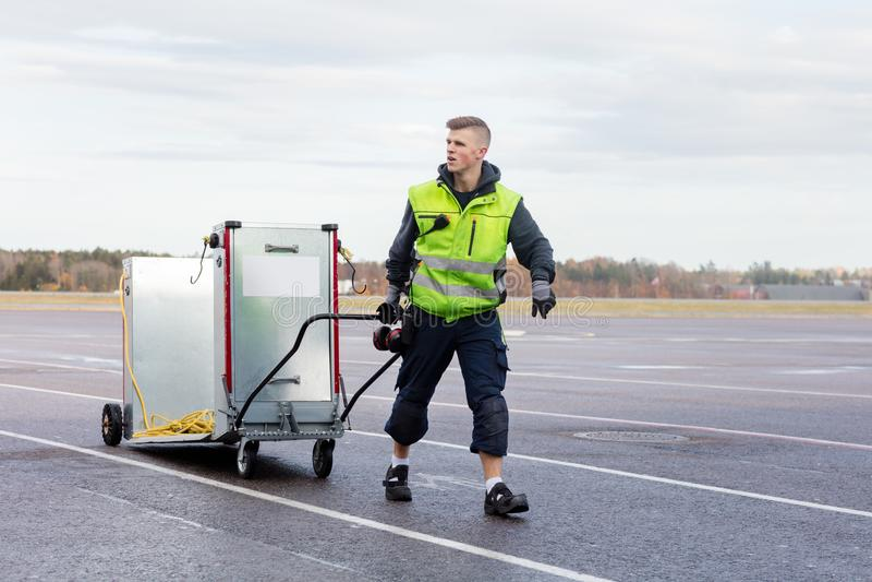 Arbeitskraft, die Maschine auf Warenkorb an der Flughafen-Rollbahn zieht lizenzfreie stockfotos
