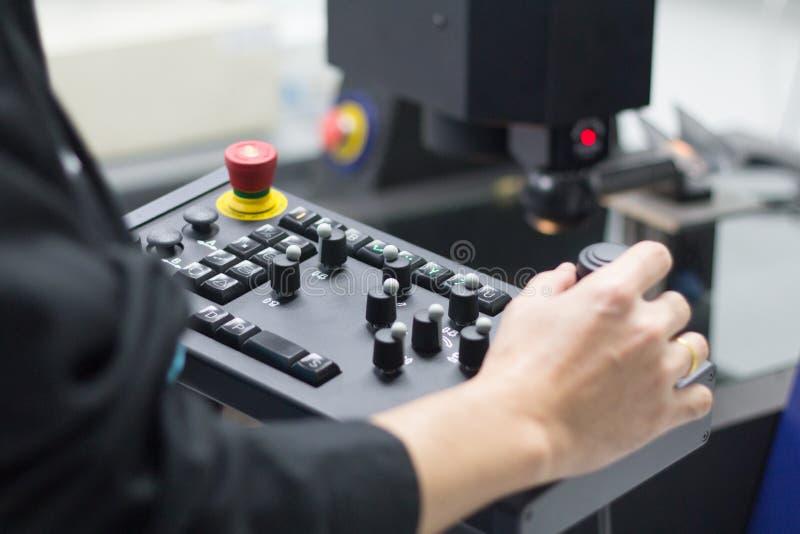 Arbeitskraft, die mit beigeordneter Messmaschine an der Werkstatt arbeitet lizenzfreie stockfotografie