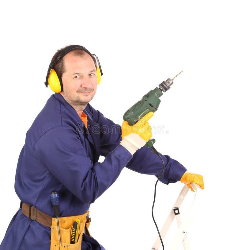 Arbeitskraft, die mit grünem Bohrgerät steht stockbild