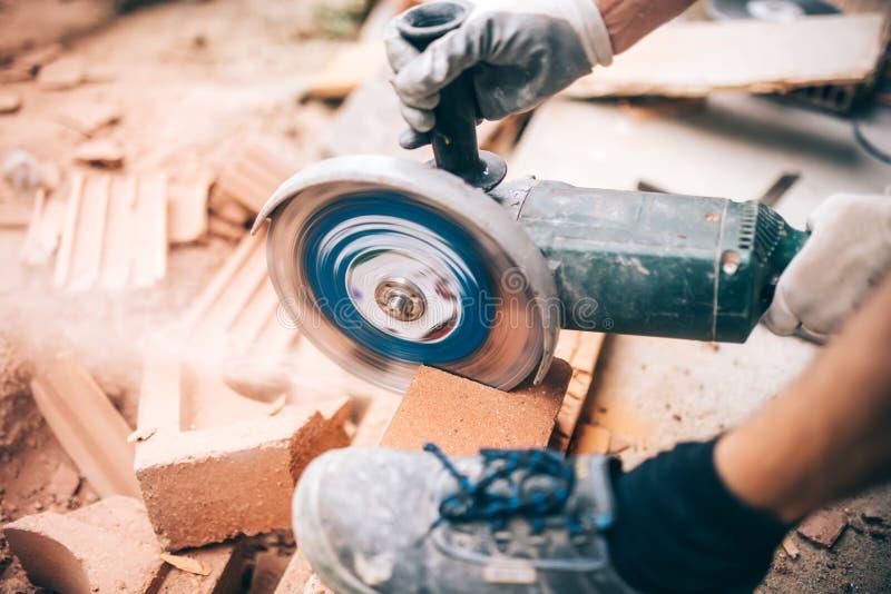 Arbeitskraft, die Schleifer auf Baustelle für den Schnitt von Ziegelsteinen, Rückstand verwendet Werkzeuge und Ziegelsteine auf N stockfoto