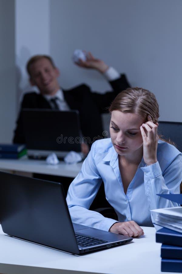 Arbeitskraft, die seins Arbeitskollege einschüchtert stockfotos