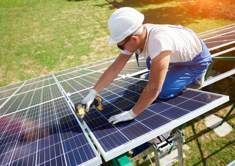 Arbeitskraft, die Sonnenkollektoren außerhalb der Karkasse des Dachs anbringt lizenzfreies stockbild