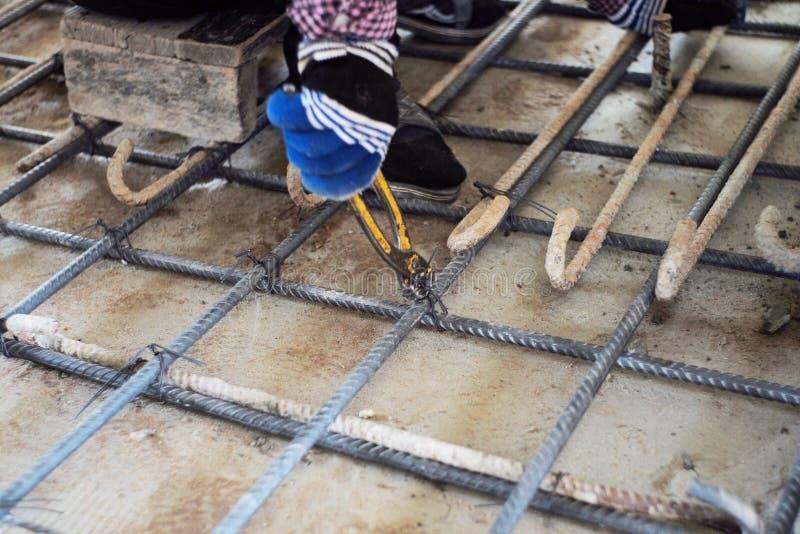 Arbeitskraft, die Stahlwerk für Verstärkung des konkreten Bodens an der Baustelle tut stockfotos