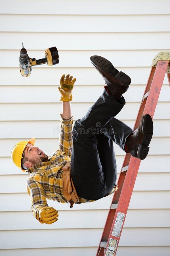Arbeitskraft, die von der Leiter fällt stockbild