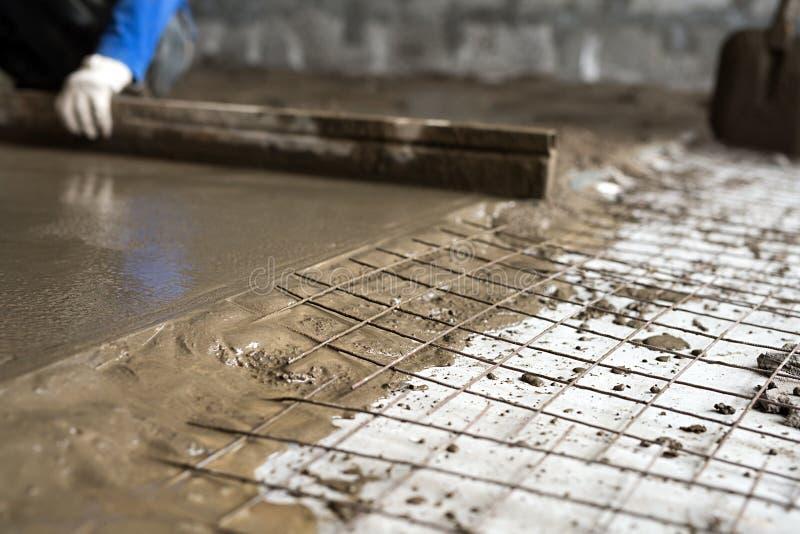 Arbeitskraft, die Zementestrich auf der Bodenansicht macht lizenzfreies stockfoto