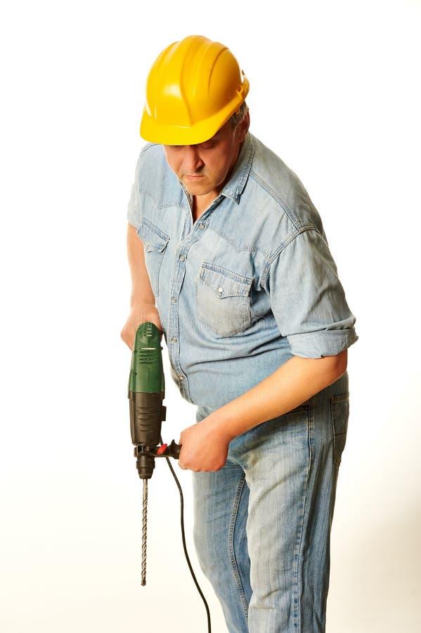 Arbeitskraft in einem gelben Hardhat mit Perforator lizenzfreie stockfotografie