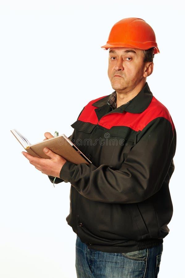 Arbeitskraft in einem orange Sturzhelm schreibt in ein Notizbuch stockfotos