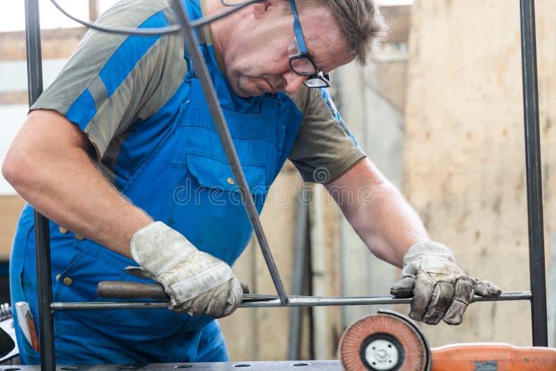 Arbeitskraft in entgratenen Werkstücken der Fabrik des Metalls stockbilder