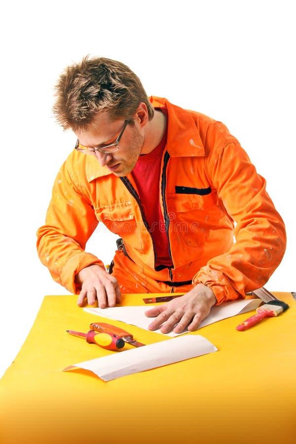 Arbeitskraft faltet sorgfältig ein Papierblatt stockfoto