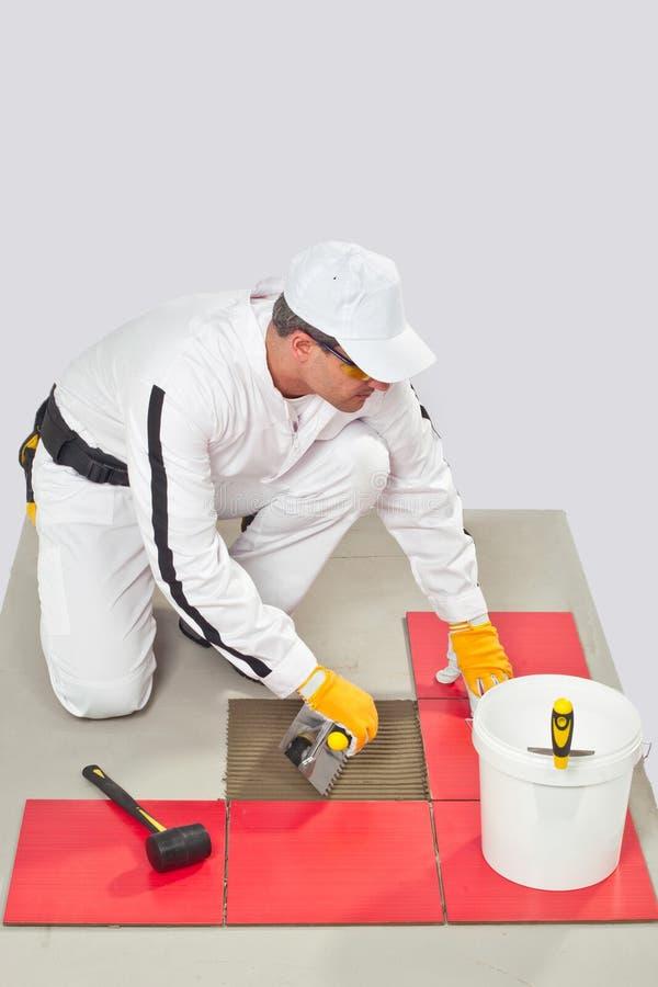 Arbeitskraft-Fliese-Kleber mit Trowel-Fliese-Fußboden stockfotografie