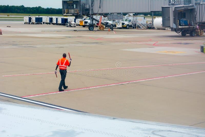 Arbeitskraft am Flughafen eine rote Sicherheits-Jacke kleidend lizenzfreie stockfotografie