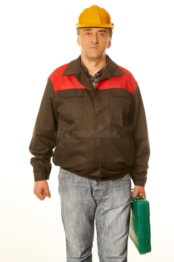 Arbeitskraft im schützenden orange Sturzhelm mit einem grünen Koffer lizenzfreies stockbild