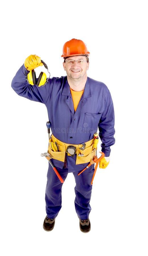 Arbeitskraft im Schutzhelm, der Ohrmuffen hält stockfoto