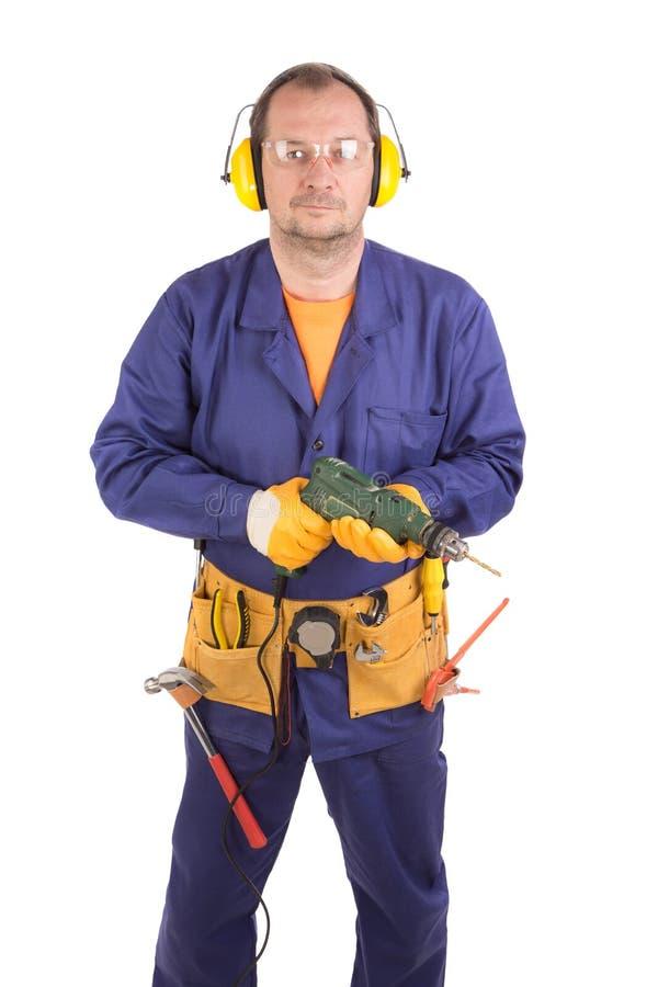 Arbeitskraft im Schutzhelmholdingbohrgerät stockbild