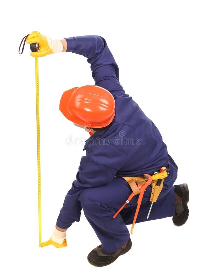 Arbeitskraft im Schutzhelmmaß mit Machthaber. lizenzfreies stockfoto