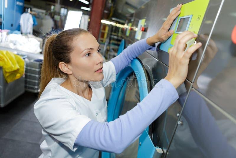 Arbeitskraft lädt Wäschereikleidung in Waschmaschine stockfotos