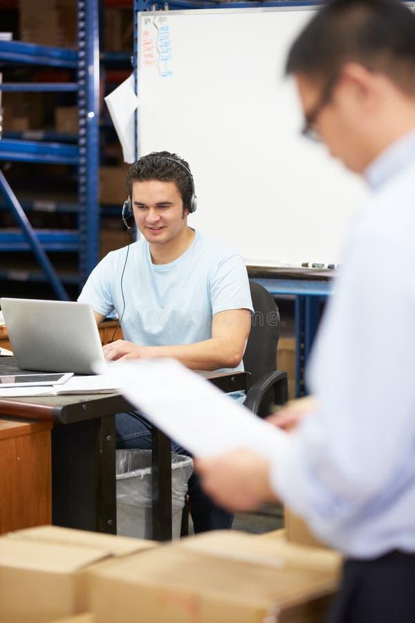 Arbeitskraft in Lager-tragendem Kopfhörer und in mit Laptop lizenzfreies stockfoto