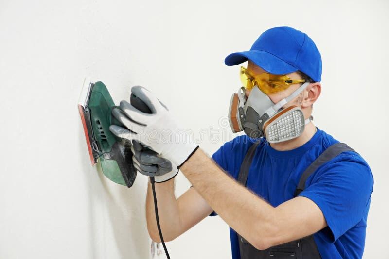 Arbeitskraft mit Augenhöhlensandpapierschleifmaschine an der Wandfüllung stockbilder