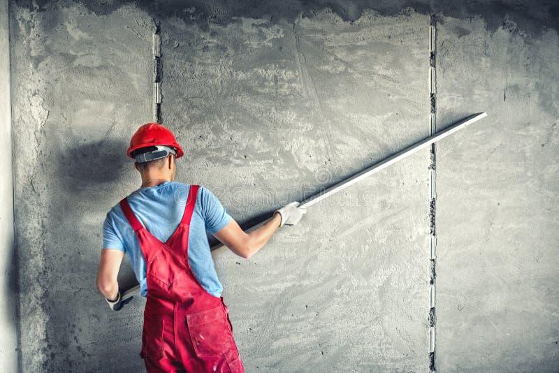 Arbeitskraft mit dem Vergipsen von Werkzeugen ein Haus erneuernd Erbauerarbeitskraft, die Industriegebäude der Fassade mit Planie stockbild