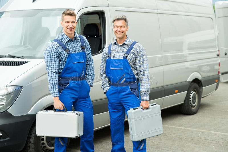 Arbeitskraft mit dem Werkzeugkasten, der in Front Of Van steht stockfotografie