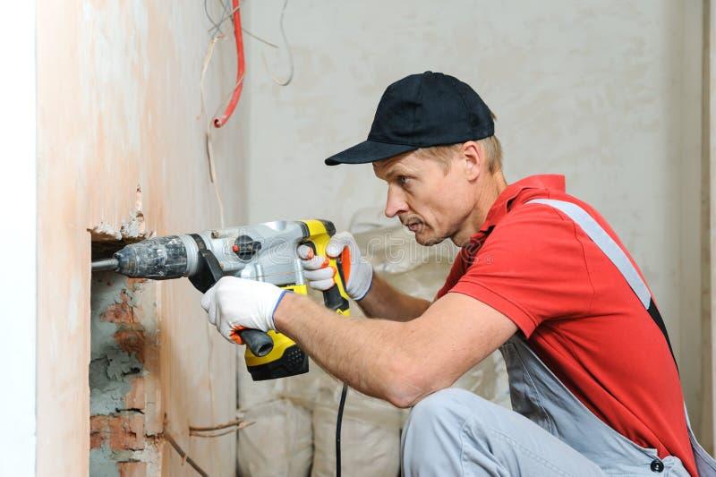 Arbeitskraft mit einem elektrischen Hammer stockbild