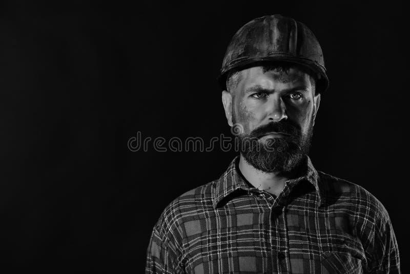 Arbeitskraft mit grobem Bild trägt schmutzigen roten Sturzhelm und kariertes Hemd Arbeits- und Schwerindustriekonzept Mann mit er lizenzfreie stockfotos