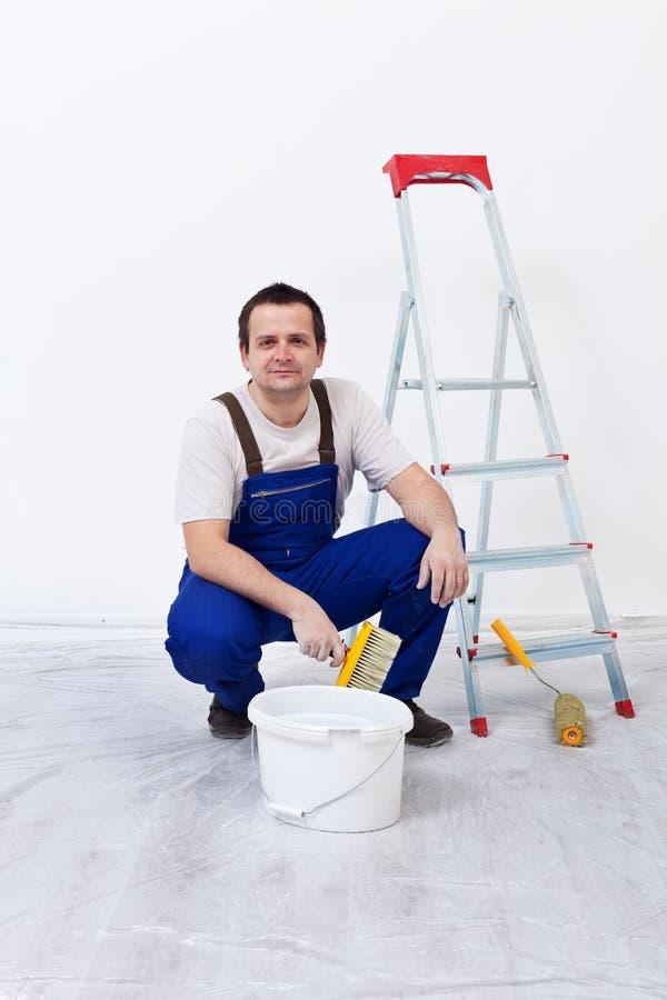 Arbeitskraft mit Lack, Pinsel und Leiter stockbild