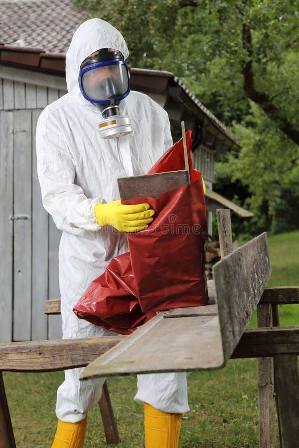 Arbeitskraft mit Maskenverpackung Asbest-Beseitigung stockfotografie
