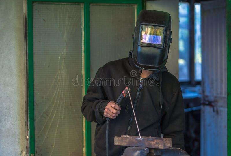 Arbeitskraft mit Schutzhandschuhen und Schutzmaskeschweißensmetallanteil an Werkstatt lizenzfreies stockbild