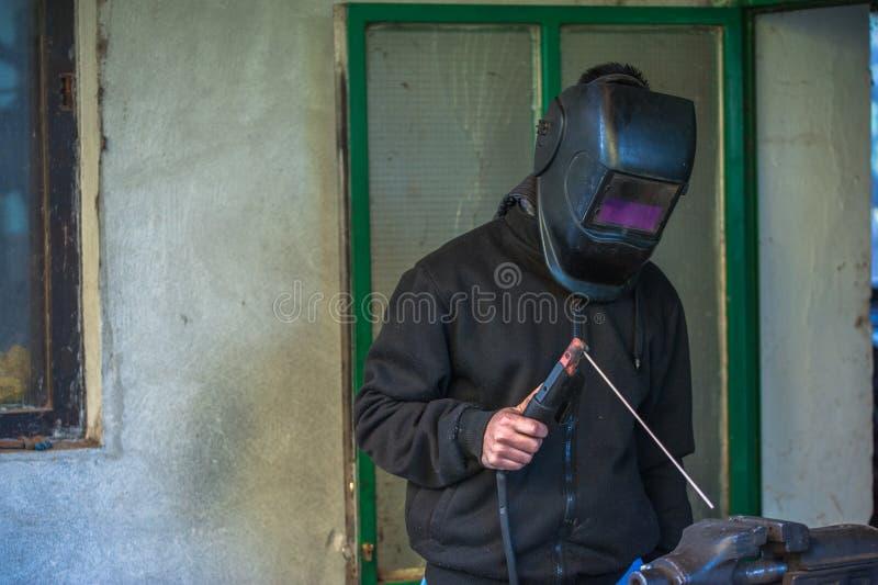 Arbeitskraft mit Schutzhandschuhen und Schutzmaskeschweißensmetallanteil an Werkstatt lizenzfreie stockfotos