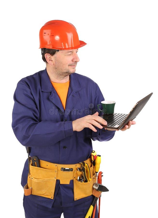 Arbeitskraft mit Tasse Kaffee und Laptop. lizenzfreie stockfotografie